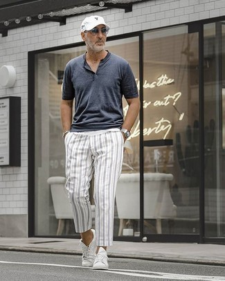 White Vertical Striped Chinos Outfits: This cool and casual look is really pared down: a charcoal henley shirt and white vertical striped chinos. This outfit is completed nicely with white canvas low top sneakers.