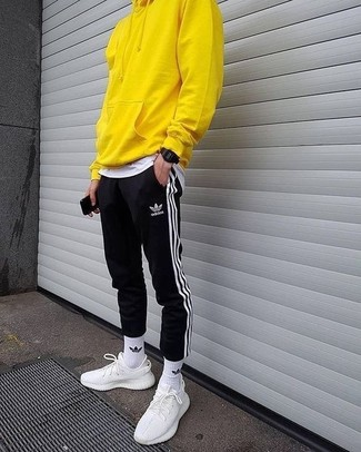 How to wear: yellow hoodie, white crew-neck t-shirt, black and white vertical striped sweatpants, white athletic shoes