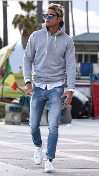 How to wear: grey hoodie, white long sleeve shirt, light blue skinny jeans, white leather low top sneakers