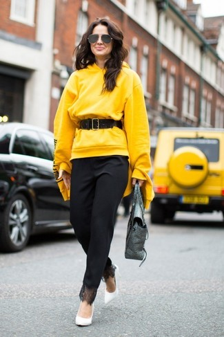 Yellow Hoodie Outfits For Women: If you're looking for a casual yet seriously chic ensemble, team a yellow hoodie with black tapered pants. Want to go all out on the shoe front? Add a pair of white leather pumps to the mix.