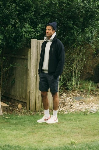 White and Red Leather Low Top Sneakers Outfits For Men: The combination of a grey hoodie and charcoal shorts makes for a solid casual menswear style. All you need now is a great pair of white and red leather low top sneakers to finish off this look.