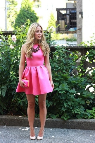 Choose a neon pink fit and flare dress and you'll look like a total babe. Dress up this look with cream leather pumps.