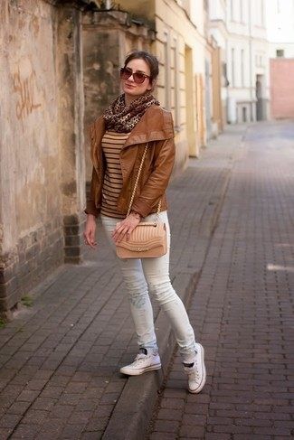 A tobacco leather jacket and white print skinny jeans are a great outfit formula to have in your arsenal. A pair of white low top sneakers brings the dressed-down touch to the ensemble.