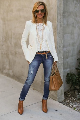 Nail glam in a jacket and blue ripped skinny jeans. Cognac leather ankle boots are a nice choice to complete the look.