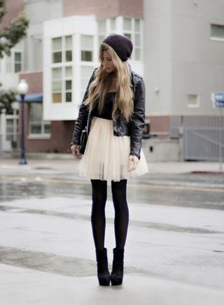 Effortlessly blurring the line between chic and casual, this combination of a black leather jacket and a white tulle mini skirt is likely to become one of your favorites. For footwear go down the classic route with black suede ankle boots.