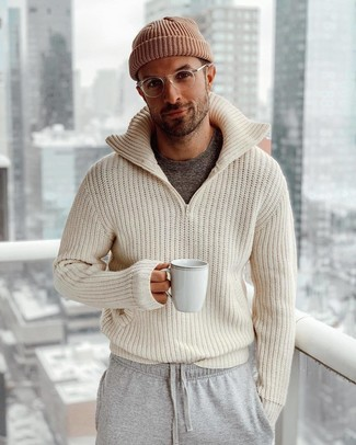 Cómo combinar: jersey con cremallera de punto en beige, camiseta con cuello circular en gris oscuro, pantalón de chándal gris, gorro marrón