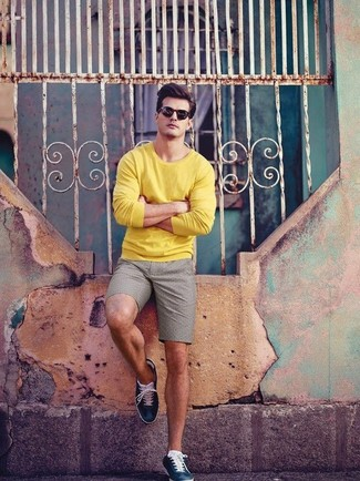 Cómo combinar: jersey con cuello circular amarillo, pantalones cortos grises, tenis de cuero azul marino, gafas de sol negras