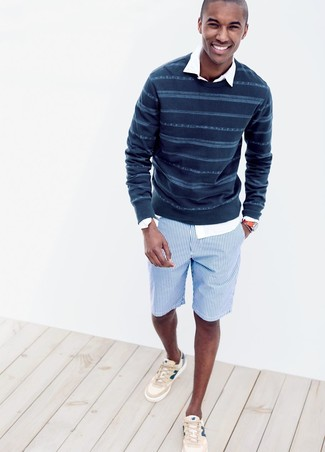 Cómo combinar: jersey con cuello circular de rayas horizontales azul marino, camisa de manga larga blanca, pantalones cortos de algodón de rayas verticales azules, tenis en beige