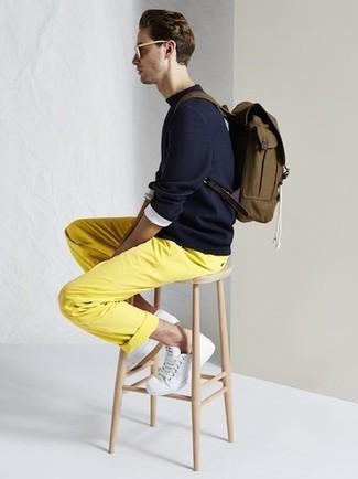 Cómo combinar: jersey con cuello circular azul marino, pantalón chino amarillo, tenis blancos, mochila de lona verde oliva