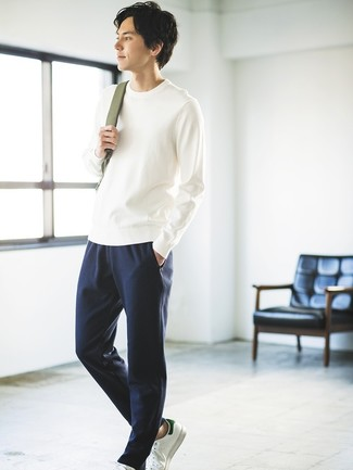 Cómo combinar: jersey con cuello circular blanco, pantalón de chándal azul marino, tenis de cuero blancos, mochila verde oliva