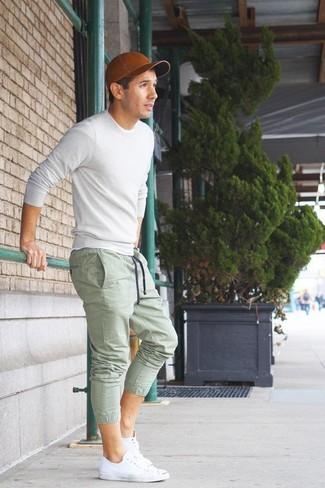 Cómo combinar: jersey con cuello circular blanco, pantalón de chándal verde, tenis blancos, gorra de béisbol de cuero marrón