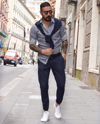 Cómo combinar: jersey con cuello circular azul marino, camisa de manga larga con print de flores en azul marino y blanco, pantalón chino azul marino, tenis de cuero blancos