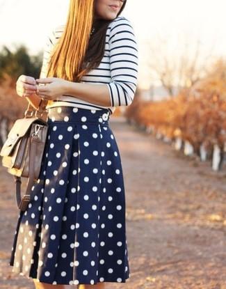 Cómo combinar: jersey con cuello circular de rayas horizontales en blanco y azul marino, falda skater a lunares en azul marino y blanco, bolso de hombre de cuero en beige