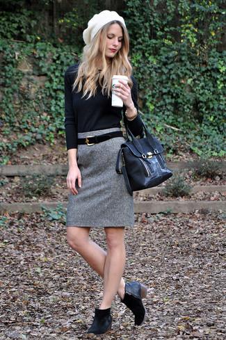 Un jersey con cuello circular negro y una falda lápiz de lana gris son el combo perfecto para llamar la atención por una buena razón. ¿Te sientes valiente? Elige un par de botines de ante negros.
