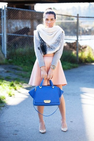 Cómo combinar: jersey con cuello circular gris, falda skater rosada, zapatos de tacón de cuero en beige, bolso de hombre de cuero azul