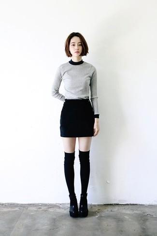 Cómo combinar: jersey con cuello circular gris, minifalda negra, sandalias de tacón de cuero gruesas negras, calcetines hasta la rodilla negros