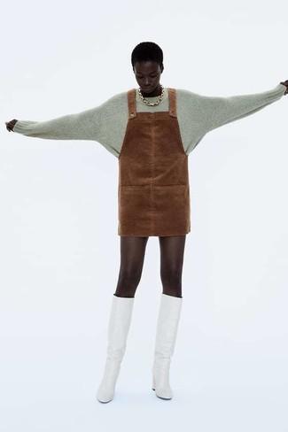 Cómo combinar: jersey con cuello circular gris, pichi de ante marrón, botas de caña alta de cuero blancas, collar dorado