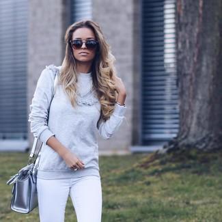 Cómo combinar: jersey con cuello circular gris, vaqueros pitillo blancos, bolso bandolera de cuero plateado, gafas de sol marrónes