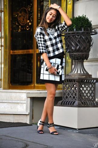 Opta por la comodidad en un jersey con cuello circular de tartán en negro y blanco y una minifalda a cuadros blanca y negra. Con el calzado, sé más clásico y elige un par de sandalias de tacón de cuero negras y blancas.
