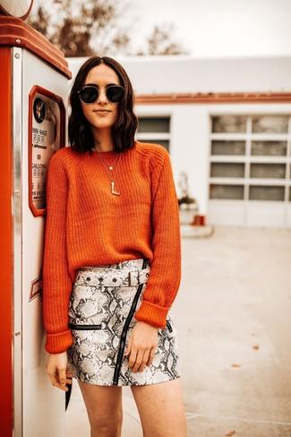 Cómo combinar: jersey con cuello circular naranja, minifalda de cuero con print de serpiente gris, gafas de sol en negro y dorado, colgante dorado