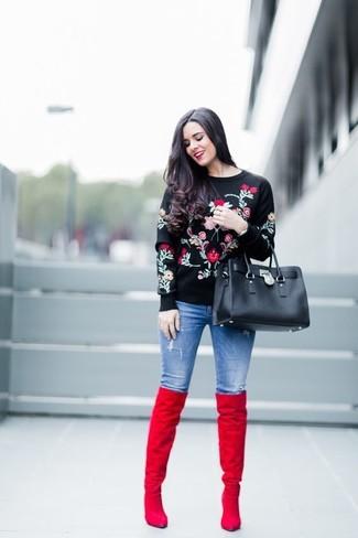 Cómo combinar: jersey con cuello circular con print de flores negro, vaqueros pitillo desgastados azules, botas sobre la rodilla de ante rojas, bolsa tote de cuero negra