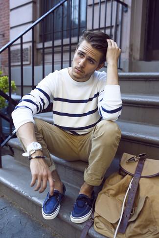 Cómo combinar: jersey con cuello circular de rayas horizontales en blanco y azul marino, pantalón chino marrón claro, náuticos de lona azules, mochila marrón claro