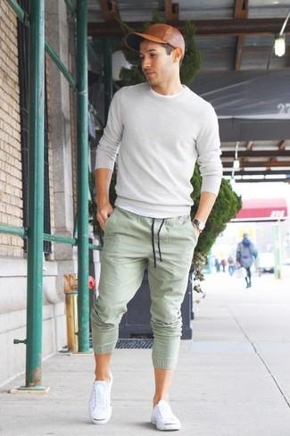 Cómo combinar: jersey con cuello circular gris, pantalón de chándal en verde menta, tenis blancos, gorra de béisbol de cuero marrón
