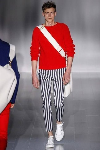 Cómo combinar: jersey con cuello circular rojo, pantalón chino de rayas verticales en negro y blanco, tenis blancos, bolso mensajero de lona blanco