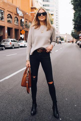 Cómo combinar: jersey con cuello circular en beige, vaqueros pitillo desgastados negros, botines de cuero negros, bolsa tote de cuero en tabaco