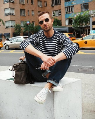 Cómo combinar: jersey con cuello circular de rayas horizontales en azul marino y blanco, vaqueros azul marino, tenis de lona blancos, bolso mensajero de cuero en marrón oscuro