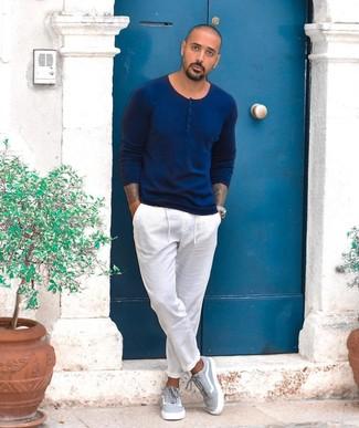 Cómo combinar: jersey con cuello henley azul marino, pantalón chino blanco, tenis de lona grises