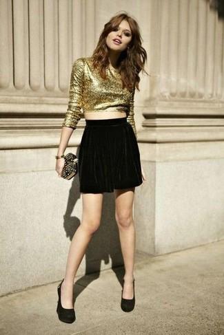 Cómo combinar: jersey corto dorado, falda skater de terciopelo negra, zapatos de tacón de ante negros, cartera sobre de cuero con tachuelas negra