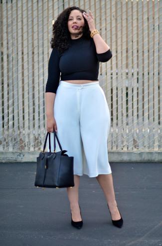 Cómo combinar: jersey corto negro, falda pantalón blanca, zapatos de tacón de ante negros, bolsa tote de cuero negra