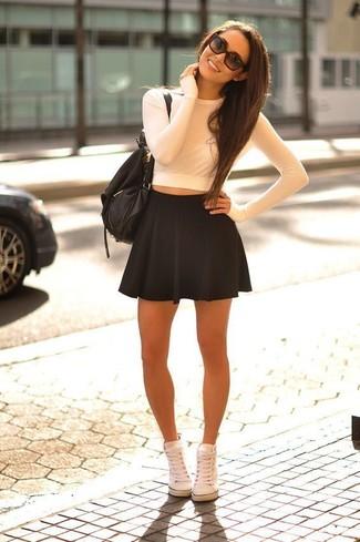 Cómo combinar: jersey corto blanco, falda skater negra, zapatillas altas blancas, mochila de cuero negra