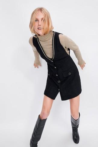 Cómo combinar: jersey de cuello alto en beige, pichi negro, botas de caña alta de cuero negras