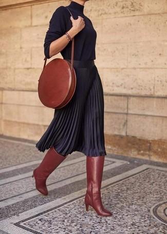 Cómo combinar: jersey de cuello alto negro, falda midi plisada negra, botas de caña alta de cuero en tabaco, bolso bandolera de cuero en tabaco