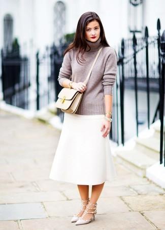 Cómo combinar: jersey de cuello alto gris, falda midi blanca, zapatos de tacón de cuero con tachuelas grises, bolso bandolera de cuero en beige