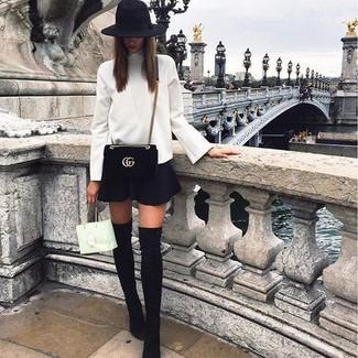 Cómo combinar: jersey de cuello alto blanco, falda skater negra, botas sobre la rodilla de ante negras, bolso bandolera de ante negro