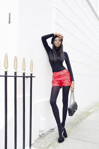 Cómo combinar: jersey de cuello alto negro, pantalones cortos de cuero rojos, zapatos de tacón de ante gruesos negros, bolso de hombre de cuero acolchado negro