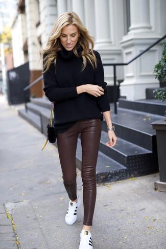 Cómo combinar: jersey de cuello alto negro, pantalones pitillo de cuero en marrón oscuro, tenis de cuero blancos, bolso bandolera de ante negro