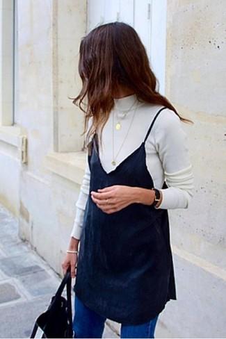 Cómo combinar: jersey de cuello alto blanco, vestido camisola negro, vaqueros azules, bolsa tote de cuero negra