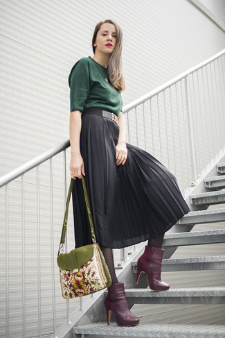 Cómo combinar: jersey de manga corta verde oscuro, falda midi de gasa plisada negra, botines de cuero morado, bolso bandolera bordado verde oliva