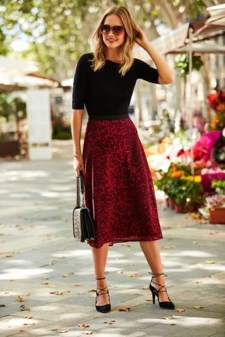 Cómo combinar: jersey de manga corta negro, falda midi de leopardo roja, zapatos de tacón de ante negros, bolso de hombre de cuero acolchado negro