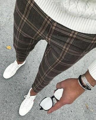 Cómo combinar: jersey de ochos blanco, pantalón chino a cuadros gris, tenis de lona blancos, pulsera plateada