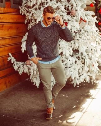Cómo combinar: jersey de ochos en gris oscuro, camisa vaquera celeste, pantalón chino verde oliva, botas para la nieve de cuero marrónes