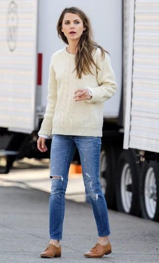 Cómo combinar: jersey de ochos en beige, camiseta de manga larga blanca, vaqueros pitillo desgastados azules, zapatos oxford de cuero marrón claro