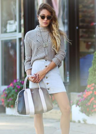 Cómo combinar: jersey de ochos en beige, falda con botones blanca, bolsa tote de cuero en negro y blanco, colgante dorado