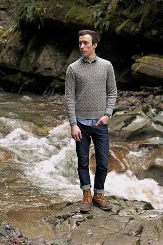 Cómo combinar: jersey de ochos gris, camisa de manga larga de cambray azul, vaqueros azul marino, botas para la nieve marrón claro