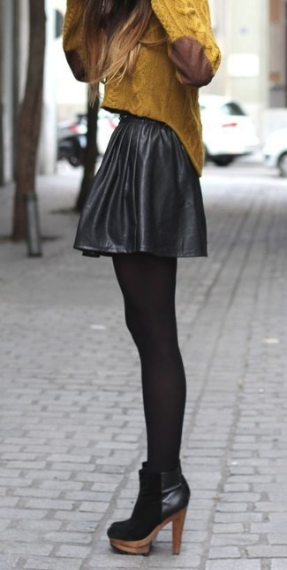 Cómo combinar: jersey de ochos mostaza, falda skater de cuero negra, botines de ante negros, medias negras