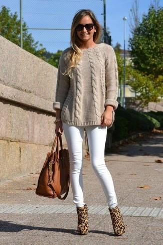Cómo combinar: jersey de ochos en beige, vaqueros pitillo blancos, botines de pelo de becerro de leopardo marrón claro, bolsa tote de cuero marrón